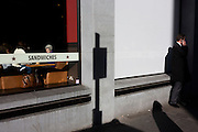 Lunchtime diners eat inside a Pret-a-Manger restaurant and man on phone in strong sunlight on London street corner.