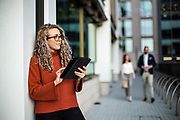Woman using a tablet stood outside office buildings in the centre of St Helier town, Jersey, CI