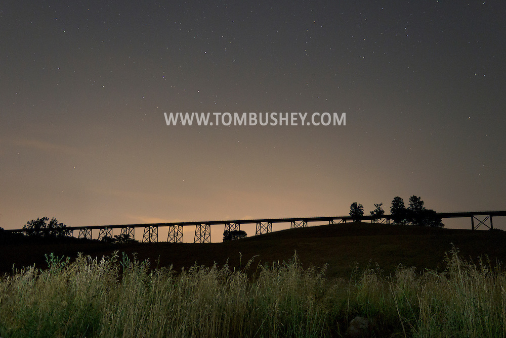 Salisbury Mills, New York - Stars in the sky and light pollution near the horizon over the Moodna Viaduct railroad trestle on July 8, 2012. The grass in the foreground was lit by a flashlight during the long exposure.