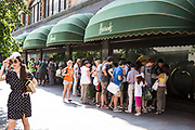 Groups of tourists gather and look through the shop window of the world famous Harrods shop in Knightsbridge, London, United Kingdom.