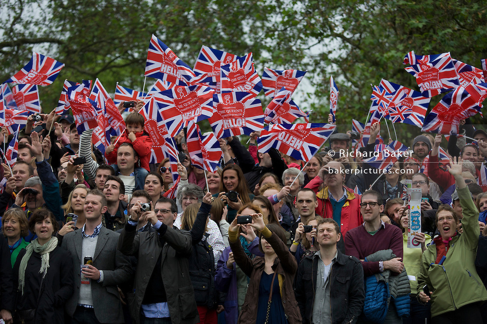 Waving their flags, the great British public brave bad weather to celebrate the Queen's Diamond Jubilee flotilla on the river Thames. 1,000 boats made their way past Battersea Park, London including their reigning monarch of 60 years and other members of the royal family during a weekend of official festivities and street parties.