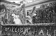 """1101-C5-33 Cotillion Hall float, Rose Festival parade, June 13, 1941. In the background is Rich's Cigar Store, SW 6th & Washington. Dupont nitrate 35mm film. Reconstructed identification, dated 1941 by comparing Retail Trade Bureau float with photo in Oregonian 6/14/41 pg. 10. The """"Cotillion Ballroom"""" float is identified in the list of floats published the day of the parade in the Oregonian, 6/13/41 pg. 8, col. 4. (The Cotillion Ballroom is now the Crystal Ballroom)"""