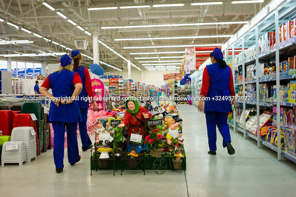 20150826 Tiraspol,  Moldova, Transnistria Three women in blue and red walk in the Sheriff hypermarket, the biggest supermarket of the country, while passing by the garden gnomes deparment