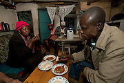 Roseline Amondi, a mother of four and microloan recipient who runs a small restaurant in the Kibera slum, Nairobi, eats at her restaurant with her neighbor, Kennedy Mbori. (From the book What I Eat: Around the World in 80 Diets.) MODEL RELEASED.
