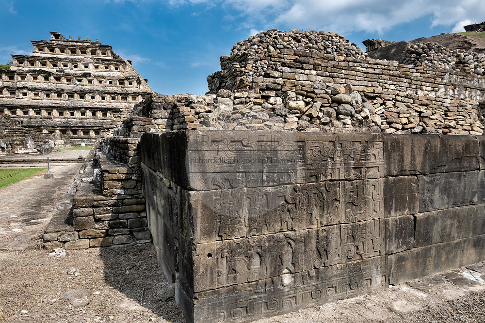 Carved relief panels on the walls of the South Ballcourt with the Pyramid of the Niches on the left at the pre-Columbian archeological complex of El Tajin in Tajin, Veracruz, Mexico. El Tajín flourished from 600 to 1200 CE and during this time numerous temples, palaces, ballcourts, and pyramids were built by the Totonac people and is one of the largest and most important cities of the Classic era of Mesoamerica.