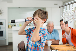 Boy looking through telescope watched by father and grandfather