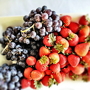 """Fresh purple grapes and red strawberries on a white plate.<br /> <br /> For all details about sizes, paper and pricing starting at $85, click """"Add to Cart"""" below."""