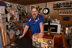 EXCLUSIVE: An Australian man has created his own Outback outpost 11,000 miles from home on the Shetland Islands – and he even has WALLABIES. Tasmanian Dave Kok, 42, has built his own Aussie oasis on the Scottish archipelago after deciding to settle there when he was travelling Europe. Now Dave lives with his Shetland native wife Louise, 38, and two daughters Caitlin, 11, and Ruby, aged four. Social care worker Dave came to the islands in the late 90s and since 2016 has been building his own watering hole choc-full of Australiana on the island of Burra. Dave's place 'The Outpost' is a renovated wooden porta cabin filled with Tasmanian beers, Tim Tams, books on bush craft and Aussie Rules sporting memorabilia. Locals use the Outpost as their local bar and meeting place, as the nearest pub or café is three bridges and three islands away. And visitors can now enjoy the Outpost's wallabies Ned and Kelly who David brought to the island this winter. Based on the Shetland Islands latitude the marsupials could be the most northerly of their species anywhere on the planet. Dave said visiting Australians are often surprised to find the antipodean paradise in such a remote location. 16 Feb 2018 Pictured: Pic from Dave Donaldson/ Magnus News Agency. Pic shows David Kok in his Aussie-themed Outpost in the Shetland Islands. An Australian man has created his own Outback outpost 11,000 miles from home on the Shetland Islands – and he even has WALLABIES. Tasmanian David Kok, 42, has built his own Aussie oasis on the Scottish archipelago after deciding to settle there when he was travelling Europe. Now David lives with his Shetland native wife Louise and two daughters Caitlin, 11, and Ruby, aged four. Social care worker David came to the islands in the late 90s and has built his own watering hole choc-full of Australiana on the island of Burra. David's place 'The Outpost' is a renovated wooden porta cabin filled with Tasmanian beers, Tim Tams, books on bush craft an