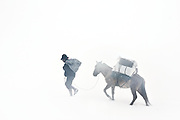 A man leads his mule, loaded with supplies purchased in Cuzco, through a blizzard and over a high pass enroute to the extant Quechua-speaking Incan village of Q'eros in the Peruvian Andes on September 14, 2005.
