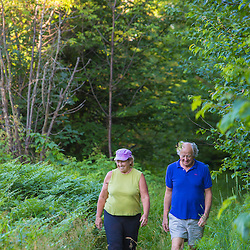 A couple walks on a woodland trail in Duxbury, Vermont.