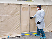 "16 MARCH 2020 - DES MOINES, IOWA: A public health employee in protective clothing at the health screening tent on the east side of the Iowa State Capitol in Des Moines. Because of numerous reports of Coronavirus in Iowa, the governor is suspending the legislative session for 30 days. It was scheduled to run until mid-April. Sunday night, the Governor announced that the state health department had recorded ""community spread"" in Des Moines. As a result the State Capitol instituted mitigation measures that included mandatory health screening for everyone going into the building, canceling group tours of the building, and closing the souvenir shop and snack bar.     PHOTO BY JACK KURTZ"