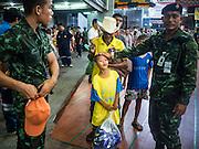 30 AUGUST 2016 - BANGKOK, THAILAND:         Thai soldiers joke with a child waiting to get into a food distribution event at the Poh Teck Tung shrine for the end of Hungry Ghost Month in Bangkok. Chinese temples and shrines in the Thai capital host food distribution events during Hungry Ghost Month, during the 7th lunar month, which is usually August in the Gregorian calendar.     PHOTO BY JACK KURTZ