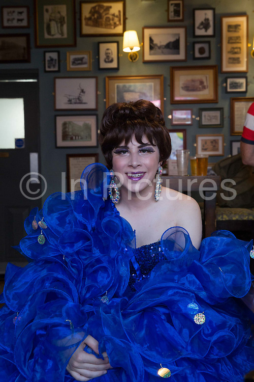 A smiling man sitting in a pub dressed in a flamboyant bright blue dress during the Manchester Pride Parade on the 25th August 2018 in Manchester in the United Kingdom. The Manchester Pride is an annual LGBT pride festival and parade held each summer in the city of Manchester, England.