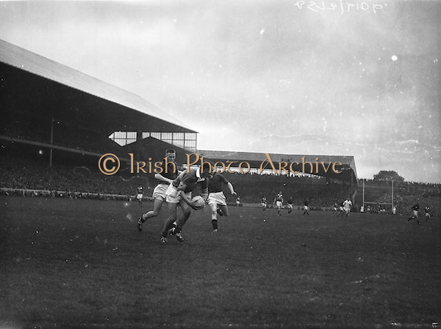 Kerry full back N. Sheehy, gets possession of the ball but is followed by Down's A Hayden and P. O'Hagan during the All Ireland Senior Gaelic Football Final Kerry v Down in Croke Park on the 22nd September 1960. Down 2-10 Kerry 0-8.