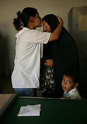 Alyaa Abdul Hassan Abbood, 23, a translator, tries to comfort Beheyen Ibrahim Jar, who just found out that her husband died at the hands of a U.S. soldier, Baghdad, Iraq, Sept. 27, 2003. Abbood works with the U.S. military to mediate as Iraqi civilians come in to receive monetary compensation for damages done by American troops in Baghdad.