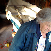 Mary Duncan of East Boothbay, Maine, walks out of her garage, with her Dory, the Nathaniel B. Palmer, on a trailer behind her. Photo by Roger S. Duncan