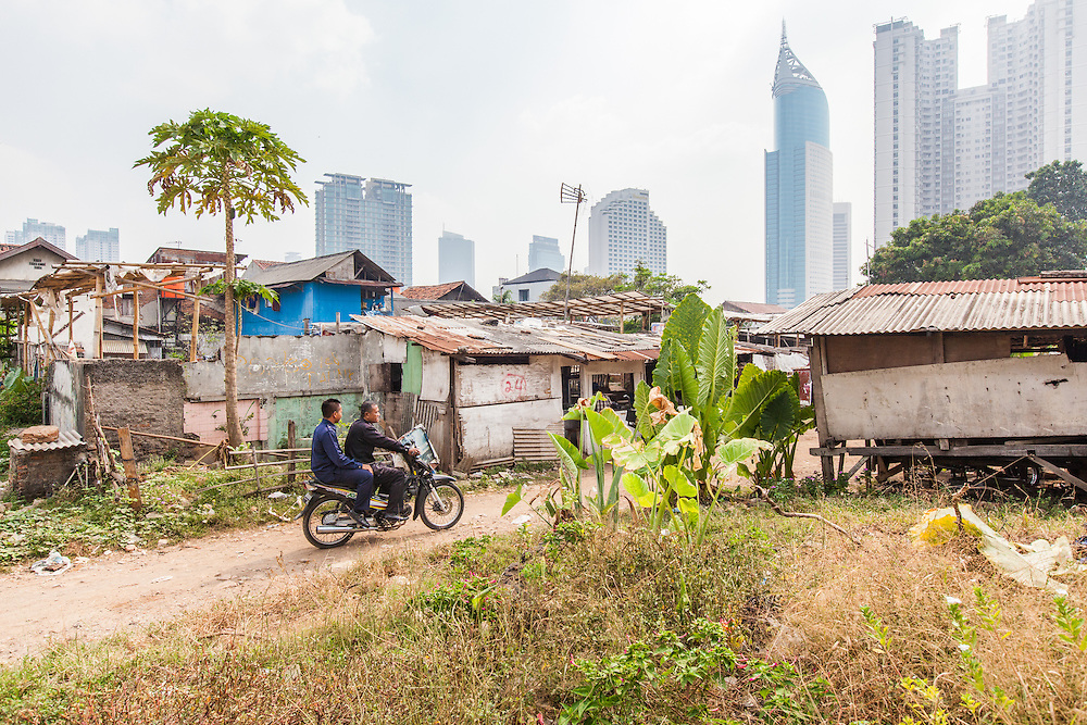 Two men on a motorcycle is seen in Karet Bivak neighborhood.  In the background is the BNI Tower and Sudirman Park, an upscale apartment complex. <br /> <br /> Despite the slowdown in the economy prices and rents are still rising in Jakarta.  Nevertheless, no big project have stopped.  The pace of construction is slow since the city has thousands of acres of one and two-story houses with multiple owners and no easy way to purchase and redevelop them.  September 20, 2013.