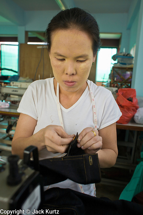 """19 FEBRUARY 2008 -- SANGKLABURI, KANCHANABURI, THAILAND:  WAWA, a Burmese refugee, works in the sewing shop at Baan Unrak Children's Home in Sangklaburi, Thailand. Baan Unrak children's home and school, established in 1991 in Sangklaburi, Thailand, gives destitute children and mothers a home and career training for a better future. Baan Unrak, the """"Home of Joy,"""" provides basic needs to well over 100 children, and  abandoned mothers. The home is funded by donations and the proceeds from the weaving and sewing shops at the home. The home is a few kilometers from the Burmese border. All of the women and children at the home are refugees from political violence and extreme poverty in Burma, most are Karen hill tribe people, the others are Mon hill tribe people. The home was started in 1991 when Didi Devamala went to Sangklaburi to start an agricultural project. An abandoned wife asked Devmala to help her take care of her child. Devmala took the child in and soon other Burmese women approached her looking for help.    Photo by Jack Kurtz"""