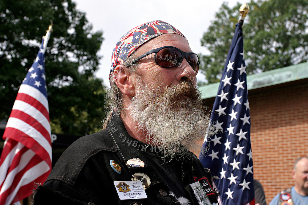 Member of the Patriot Guard Riders holding portrayed prior to the funeral service of Sgt. Ian T. Sanchez, in Staten Island, NY., on Tuesday, June 27, 2006. Sgt. Sanchez, a 26-year-old American serviceman was killed by a roadside bomb in the Pech River Valley, Afghanistan. The Patriot Guard Riders is a diverse amalgamation of riders from across the United States of America. Besides a passion for motorcycling, they all have in common an unwavering respect for those who risk their lives for the country's freedom and security. They are an American patriotic group, mainly but not only, composed by veterans from all over the United States. They work in unison, calling upon tens of different motorcycle groups, connected by an internet-based web where each of them can find out where and when a 'Mission' is called upon, and have the chance to take part. This way, the Patriot Guard Riders can cover the whole of the United States without having to ride from town to town but, by organising into different State Groups, each with its own State Captain, they are still able to maintain strictly firm guidelines, and to honour the same basic principles that moves the group from the its inception. The main aim of the Patriot Guard Riders is to attend the funeral services of fallen American servicemen, defined as 'Heroes' by the group,  as invited guests of the family. These so-called 'Missions' they undertake have two basic objectives in particular: to show their sincere respect for the US 'Fallen Heroes', their families, and their communities, and to shield the mourners from interruptions created by any group of protestors. Additionally the Patriot Guard Riders provide support to the veteran community and their families, in collaboration with the other veteran service organizations already working in the field.   **ITALY OUT**