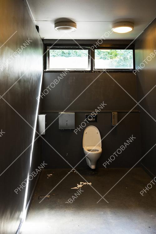 Toilet paper on floor in a dirty bathroom