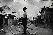 A man in a tall hat stands with his bike in a poor town in Belize.