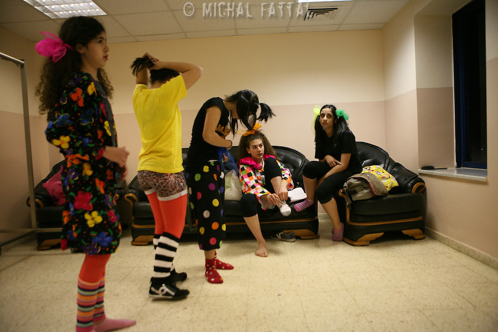 """Members of The Palestinian Circus School prepare themselves behind the scenes, before going on stage to perform the show """"Circus behind the wall"""" in Ramallah, November 20, 2009.The circus group was established in 2006, in order to give a new way of expression for Palestinians, and a new way to deliver the idea of resistance to the occupation. This performance is based on the life of Palestinians behind the separation wall. Photo by Michal Fattal/backyard"""