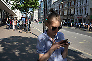 Smoking and texting along Oxford Street in London, England, United Kingdom. This is the busiest shopping district in the capital with Oxford Street being the most crowded. Crowds can be so big that many people avoid the area altogether.