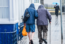 ©Licenced to London News Pictures. Aberystwyth, UK, 17/07/2018. After many weeks of almost constant sunshine and exceptionally dry weather, the rains have returned with people seen sheltering from the downpour under their umbrellas as they walk along the promenade in Aberystwyth on the west Wales coast. Photo credit: Keith Morris LNP