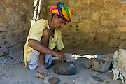 Indian potter in traditional Rajasthani turban works at home preparing clay in village of Nimaj, Rajasthan, Northern India