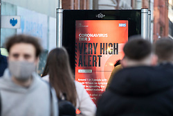 © Licensed to London News Pictures. 19/12/2020. Manchester, UK. Shoppers on Market Street, Manchester pass by a Covid sign. Photo credit: Kerry Elsworth/LNP