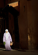 A woman carrying bread and fresh herbs in the narrow streets of the medina in Fes, Morocco