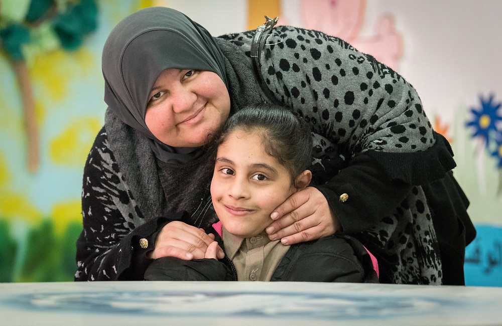 19 February 2020, Amman, Jordan: 10-year-old Bayan, a girl born with Cerebral Palsy, attends the Al Yarmouk Primary Mixed School, in the Lewa'a Al Jama'a district. Here, with her mother Eman Ahmed. Following three years in a school exclusively for children with disabilities, today she attends 4th grade at Al Yarmouk, which has recently opened up to receive her. Here, sharing a moment with her mother Eman Ahmed. The school teaches some 750 students from 1st - 6th grade, most of them Jordanian, but some also from Syria and other countries. The school has received support from the Lutheran World Federation in refurbishing their buildings and classrooms, as well as training on protection and social cohesion, including how to become more inclusive of children with disabilities.