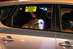 © Licensed to London News Pictures . 28/10/2018. Manchester, UK. A woman wearing a mask sits forward with her head down in the back seat of a minicab . Revellers on a night out , many in fancy dress , on the weekend before Halloween . Photo credit: Joel Goodman/LNP