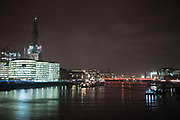 Night scene in London on a cold winter evening looking over the River Thames towards London Bridge, More London and on the left, the construction of the Shard.