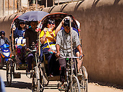 06 MARCH 2017 - KATHMANDU, NEPAL: Tourists ride a rickshaw through Kathmandu. Some local people still use the rickshaws, but more they are becoming a tourist attraction. The tourists pay the rickshaw wallas a lot more than the local people do.       PHOTO BY JACK KURTZ