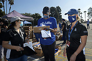 Los Angeles Dodgers community and government relations coordinator Erika Sanchez (left), community coordinator Noelle Bailey (center) and government and community affairs senior manager Patricia Sanders during Dodgers Foundation 16th annual Thanksgiving Turkey Giveaway at Dodger Stadium, Thursday, Nov. 19, 2020, in Los Angeles.