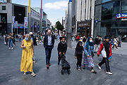 With just five more days to the official freedom day planned for the 19th July, people, many of whom are wearing face masks, come to the Bull Ring city centre retail shopping district on 14th July 2021 in Birmingham, United Kingdom. After months of lockdown, but with case numbers rising, in particular that of the Delta Variant, there is hope that life will start to return to normal, with restrictions like the compulsory wearing of face coverings in public spaces ending.