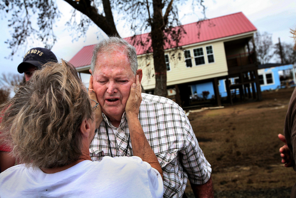 Earl Kile, an 82-year-old lifelong resident of Sabine Pass, Texas, breaks into tears when he sees his home for the first time after Hurricane Ike Friday September 19, 2008.  He hopes he can return to live in Sabine Pass, even if it means staying in a tent next to his home.  Fellow lifelong Sabine Pass resident Helena Saunders, left, comforts Kile.