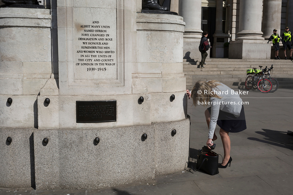 A lady changes shoes beneath the WW1 memorial at Royal Exchange, on 19th April, in the City of London, England.