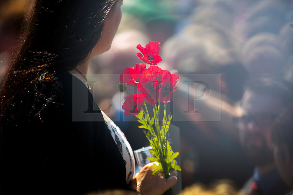 © Licensed to London News Pictures. 11/06/2015. National Memorial Arboretum, Alrewas, Staffordshire, UK. The service to mark the Rededication of the Bastion Memorial. The memorial was begun in Helmand Province in 2006, deconstructed in 2014 and now replicated at the National Memorial Arboretum in Staffordshire. Around two thousand people took part in the service including HRH Prince Harry, the Prime Minister David Cameron and senior members of the Armed Forces. Pictured, a guest carrying poppies. Photo credit : Dave Warren/LNP