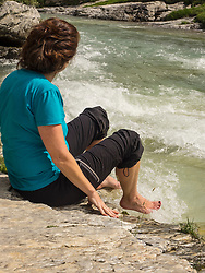 Woman hiker taking rest at riverbank of Gaube d'Estaube, France