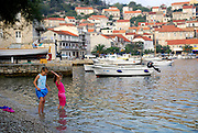 Two children (9 years old and 5 years old) wading in water, Racisce, island of Korcula, Croatia