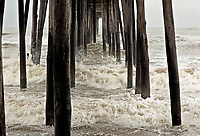 NC01270-00...NORTH CAROLINA - Wind blown surg smashing into the pillars supporting Nags Head Fishing Pier on the Outer Banks at the town of Nags Head.