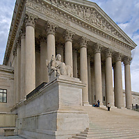 Tourists relax on the stone stairs of the U.S. Supreme Court building in Washington, DC.