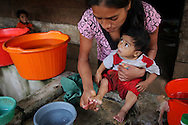 Health promotor Amarilis Miranda  washes Julio, 1, while visiting the home of  his HIV+ mother Lety, 22,   in a Guatemalan village. Miranda who is also HIV+ teaches others about simple home remedies and visits the homes of other HIV patients to answer questions, check up on their health, distribute food supplies, and help ensure that they are taking their anti-retrovirals. Sara A. Fajardo/Catholic Relief Services