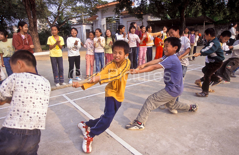 """Primary school children in a """"tug of war"""" contest during a physical education class, near Huizhou city, China"""