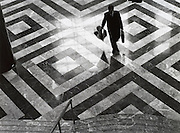 A business man walking across a square patterned floor
