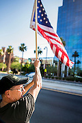 25 JUNE 2012 - PHOENIX, AZ:  BENJAMIN CAMPOS, a naturalized US citizen and supporter of immigrants' rights, waves an American flag in front of the Immigration and Customs Enforcement (ICE) offices in central Phoenix Monday. About 100 immigration supporters held a protest against ICE and continued deportations by the Obama administration. Protesters also celebrated the US Supreme Court decision to overturn most of SB1070, Arizona's tough anti-immigration law.     PHOTO BY JACK KURTZ