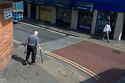 A young and healthy black man strides along the street and an infirm elderly man using a walking stick prepares to carefully cross the road, on 22nd May 2019, in Southwark, south London, England