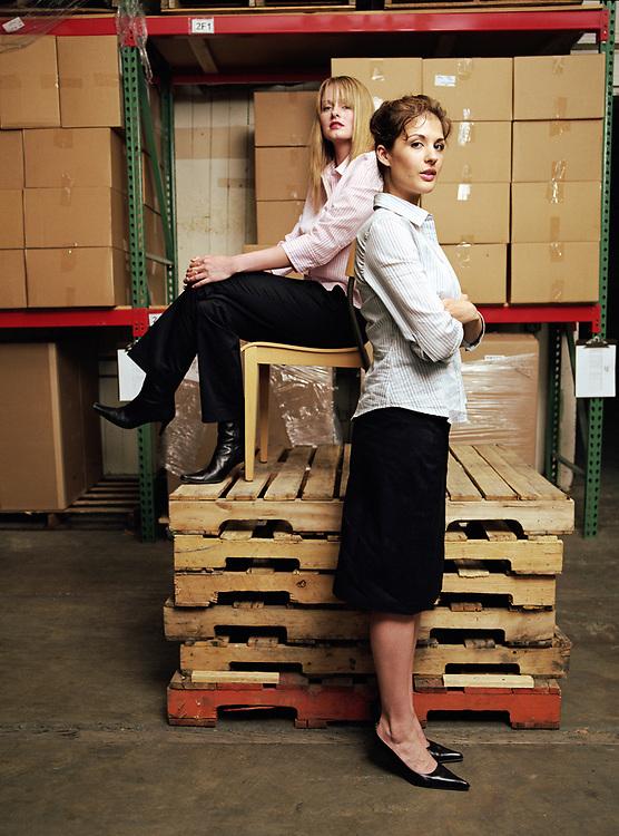 Two 20 something businesswomen in warehouse, portrait